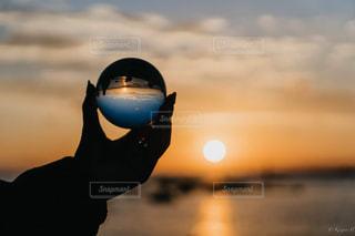 夕焼けにかざして照らされるガラス玉の写真・画像素材[2354363]