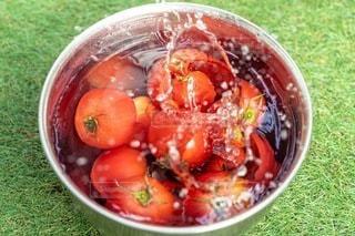 水しぶきを上げるトマトの写真・画像素材[3410155]