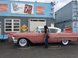 アメリカンなカレー屋さんの前に停まっているピンクの車と女性の写真・画像素材[1061894]