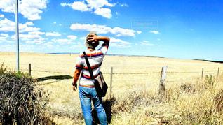 乾いた草のフィールドに立っている人の写真・画像素材[1061548]