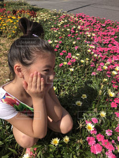 花の前に座っている少女の写真・画像素材[1116548]