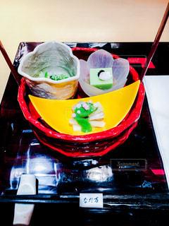 近くのテーブルの上に食べ物のボウルの写真・画像素材[1061796]