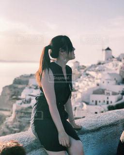 水の体の横にある岩の上に座っている女性の写真・画像素材[1281278]