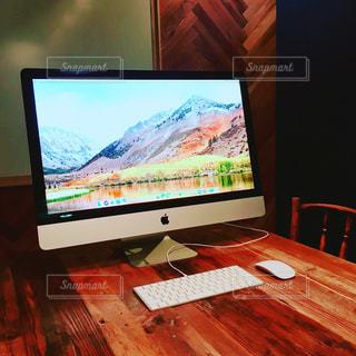木製テーブルの上のコンピューターMacのモニターの写真・画像素材[1064137]