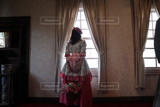 ウィンドウの前に立っている人の写真・画像素材[1108175]