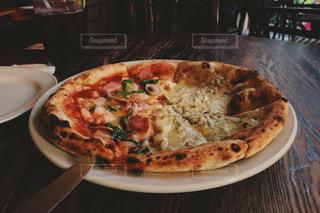 テーブルの上に座っているピザの写真・画像素材[2359322]