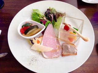 テーブルの上に食べ物のプレートの写真・画像素材[1065623]