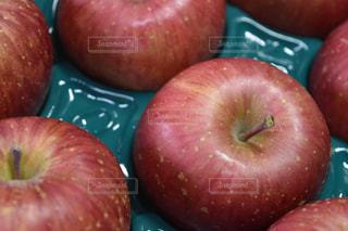 フルーツ ボウル隣に座っている赤いりんごの写真・画像素材[1065984]