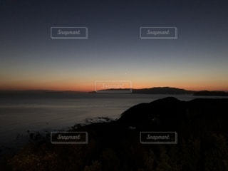 背景の山が付いている水の体に沈む夕日の写真・画像素材[1066351]