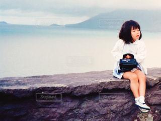 おしゃれした女の子が海をバックに岩に腰掛けてぼへーっとしている - No.1076935