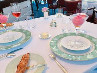 テーブルの上にワイングラスとグラス入り前菜の乗ったプレートの写真・画像素材[1081234]