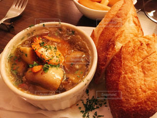 グツグツのアヒージョとフランスパンの写真・画像素材[1084789]