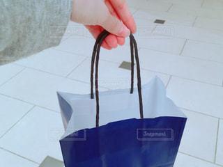 青い紙袋の手土産を持つ手の写真・画像素材[1085618]