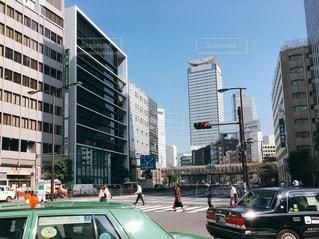 背の高い建物に囲まれたトラフィックでいっぱい車の通り都市の運転の写真・画像素材[1090891]