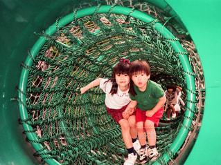 遊具のトンネルから出てくる姉弟 - No.1097430