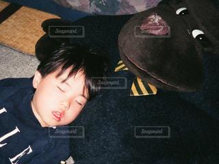 大きなゴリラのぬいぐるみを枕にお昼寝する男の子の写真・画像素材[1098948]