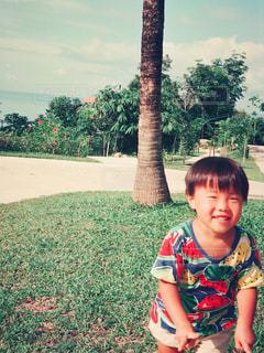 芝生ではしゃぐ小さな男の子の写真・画像素材[1100631]
