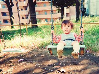 ブランコに座っている小さな男の子の写真・画像素材[1104622]