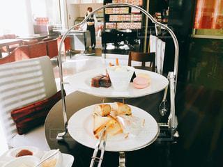 テーブルの上にアフタヌーンティーのプレートの写真・画像素材[1105027]