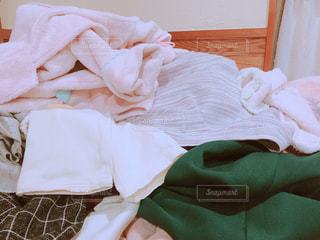 ベッドの上に溜まった洋服の写真・画像素材[1107885]