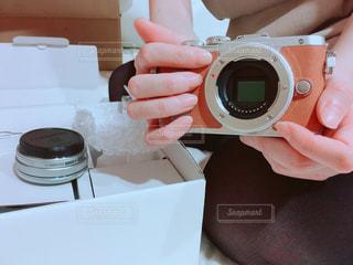 届いたミラーレスを手に取り喜ぶ女性の写真・画像素材[1121199]