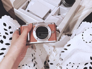 ベッドの上に座ってミラーレス一眼を開封する女性の写真・画像素材[1121233]