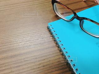 テーブルの上のリングノートと眼鏡の写真・画像素材[1534758]