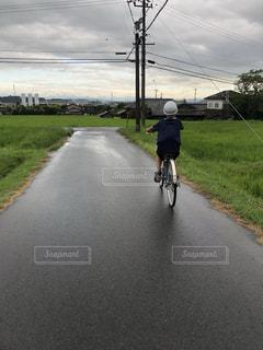雨上がりに自転車に乗る小学生の写真・画像素材[1630714]