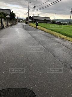 自転車で田舎道を駆け抜ける少年の写真・画像素材[1630715]