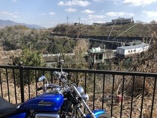 フェンスの側面に駐車しているオートバイの写真・画像素材[2738819]