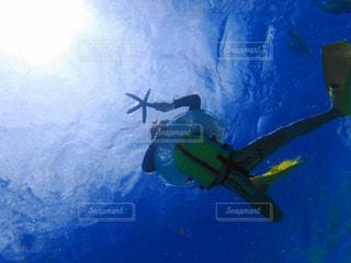 青い海に浮かぶ少年の写真・画像素材[1068128]
