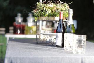ボトル入りワインとテーブルの上の花の花瓶の写真・画像素材[1068832]