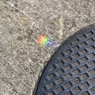 マンホールの隣に虹、いい1日の始まりの写真・画像素材[1073957]
