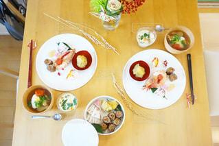 食品のプレートをテーブルに座っている人々 のグループの写真・画像素材[1074997]