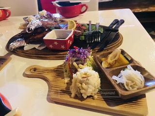 テーブルの上に食べ物のプレートの写真・画像素材[1076769]