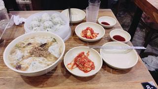 テーブルの上の皿の上に食べ物のボウルの写真・画像素材[1084453]
