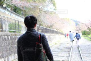 フェンスの横に立っている人の写真・画像素材[1084459]