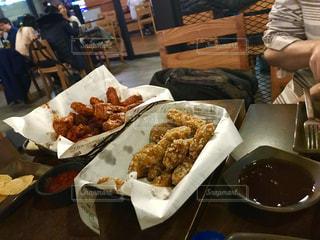 食品のプレートをテーブルに着席した人の写真・画像素材[1084463]