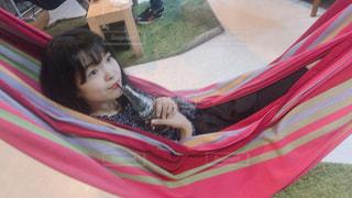 赤い毛布の上に横たわる少女の写真・画像素材[1076637]