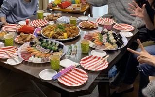 食べ物の皿を持ってテーブルに座っている人々のグループの写真・画像素材[2986606]