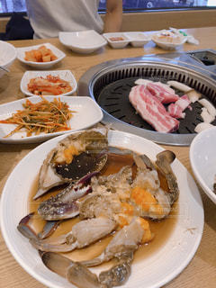 テーブルの上に食べ物のプレートの写真・画像素材[1472080]