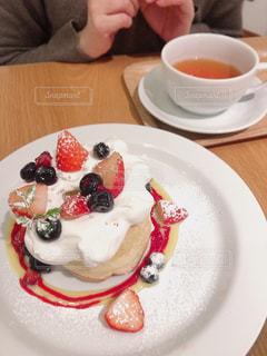 コーヒーを飲みながら皿にケーキを置くの写真・画像素材[2964188]
