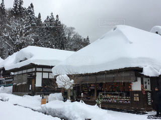 雪に覆われた茅葺屋根の家 - No.1080998