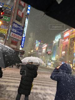 傘を持って通りを歩いている人の写真・画像素材[1081906]