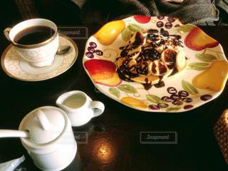 食品やコーヒー テーブルの上のカップのプレートの写真・画像素材[1098976]