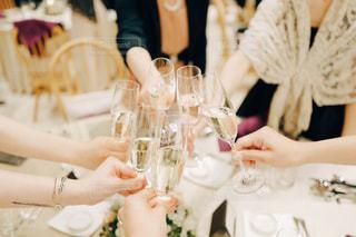 ワイングラスを持つテーブルに座っている女性の写真・画像素材[1086738]