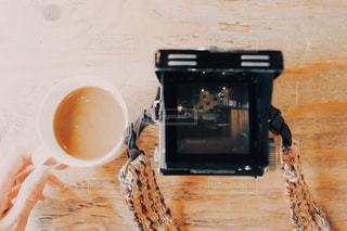テーブルの上のコーヒーとカメラの写真・画像素材[1086809]