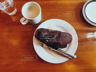 フォークと木製のテーブルの上のコーヒー カップとプレートの写真・画像素材[1788666]