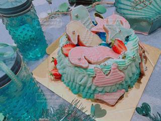 バースデー ケーキでテーブルに座っている人々 のグループの写真・画像素材[1087147]