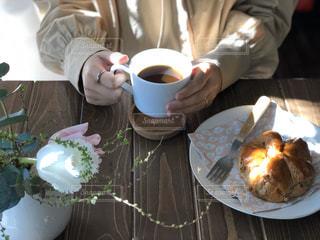 食べ物とコーヒーを飲みながらテーブルに座っている人の写真・画像素材[3012533]